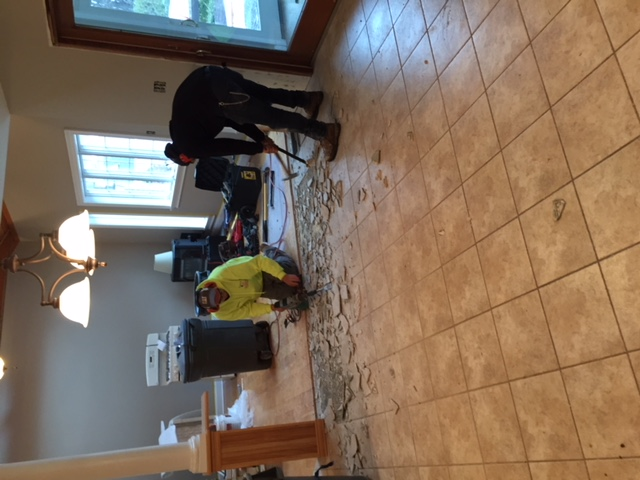 two men breaking up floor tile