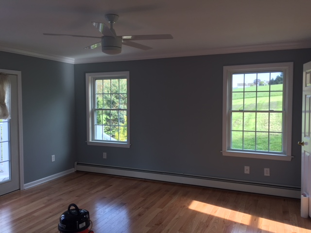 finished room with fresh paint, ceiling fan, two windows, and hardwood floors
