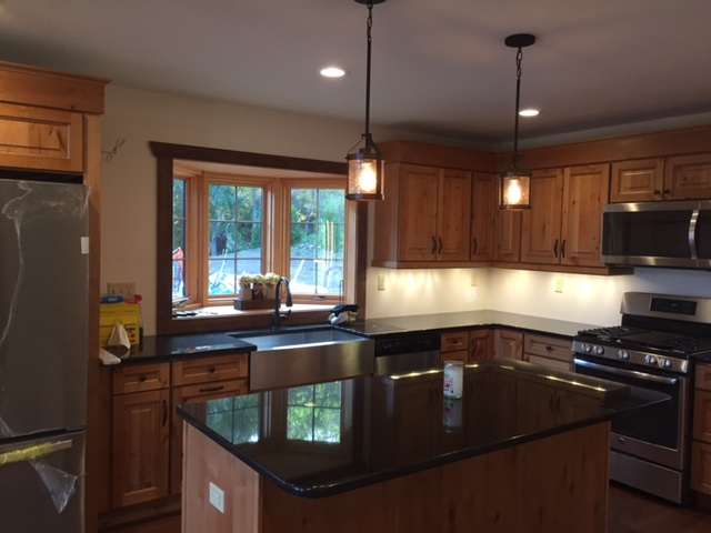 view of kitchen with wood cabinets and two hanging lights