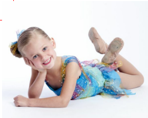 Young girl smiling wearing a dance costume and dance shoes