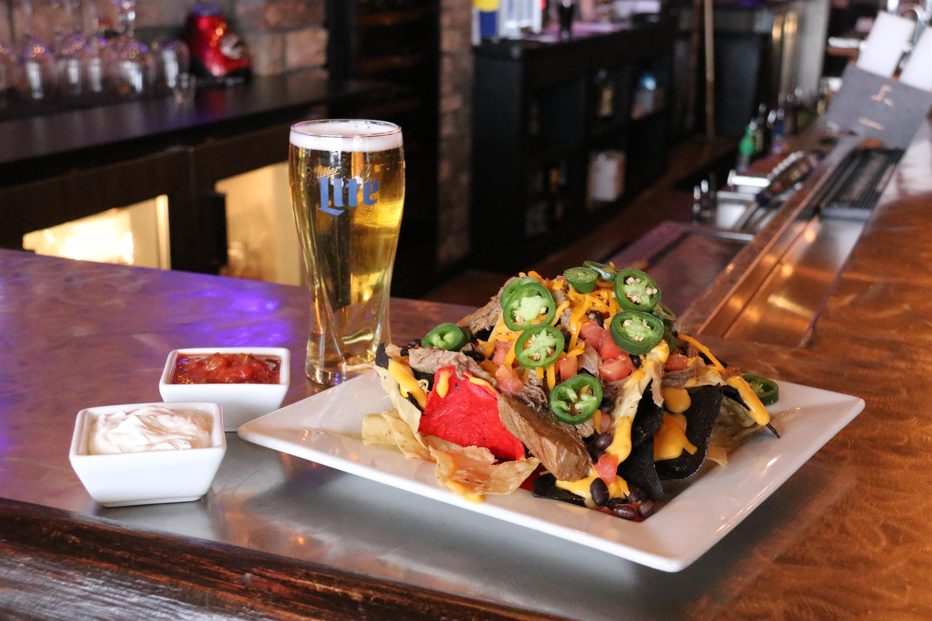 nachos covered in cheese with dressing and a glass of beer
