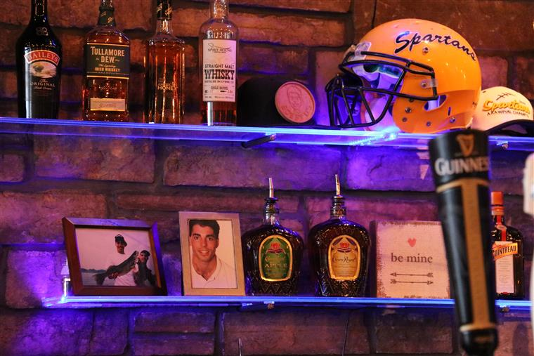 wall decorated with a football helmet, different pictures and liquor bottles