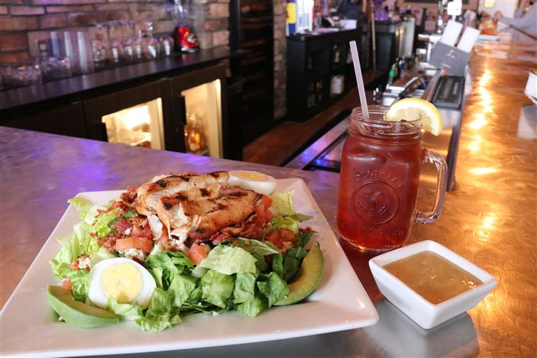 large caesar salad topped with grilled chicken, dressing on the side and a glass of tea with a lemon wedge