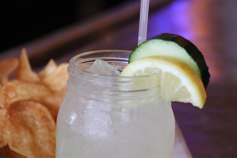 close-up view of glass of water with two lemon wedges, and chips in the background