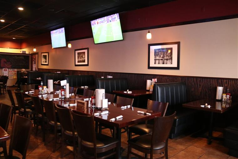 inside seating with tables and chairs, pictures along the wall and televisions mounted on the wall