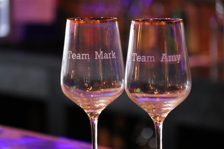 two wine glasses with team mark on one, team amy on the other