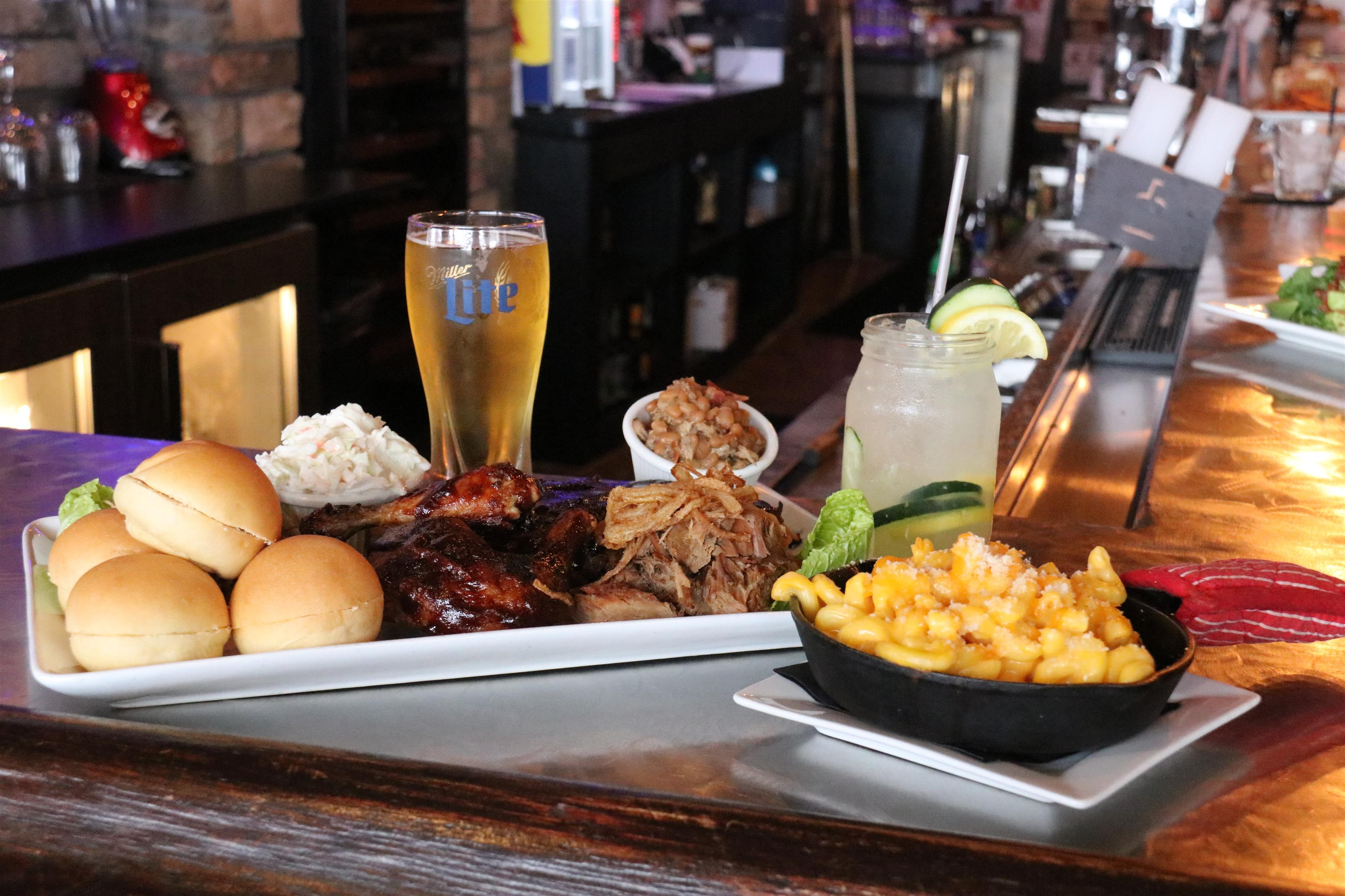 Bobby D's BBQ Sampler. ½ rack ribs, smoked brisket, pulled pork and BBQ chicken Quarter served with slider buns, creamy coleslaw, baked beans and mac & cheese skillet.
