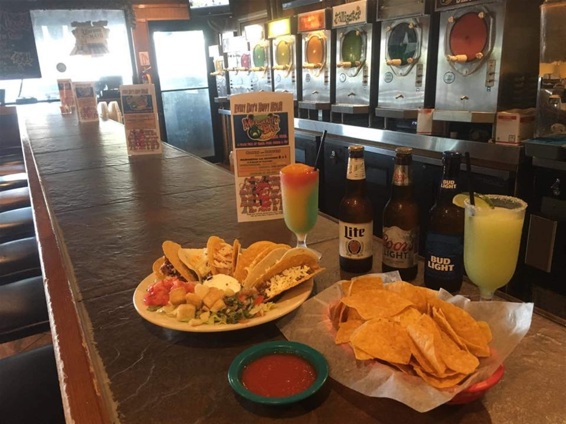 three bottles of beer with a plate of food and nacho chips on the side
