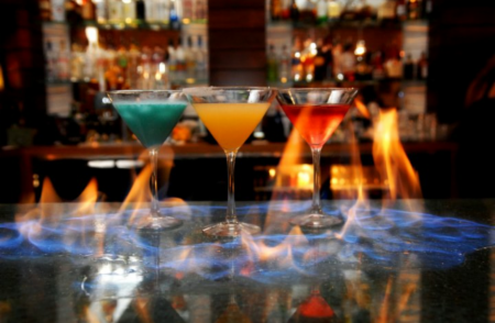 Three colorful cocktails on flaming tabletop.