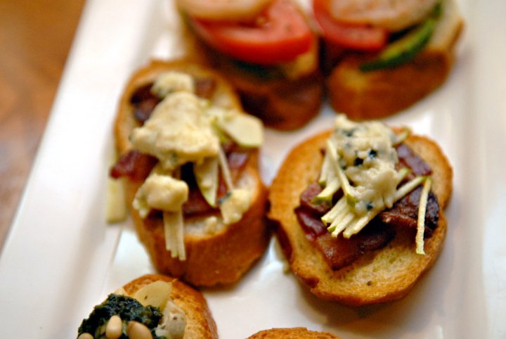 Assorted appetizer bruschettas on toasted bread.