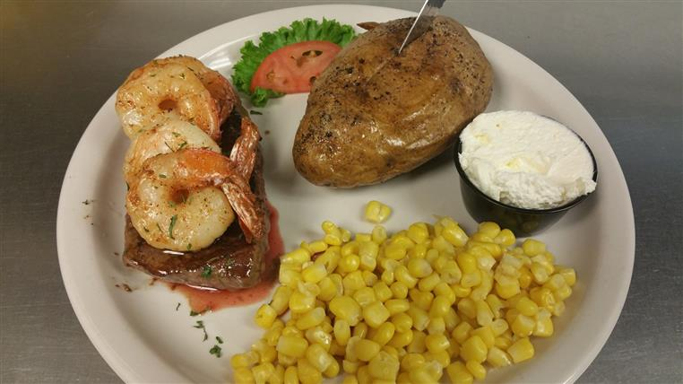 surf and turf with corn on the side and a baked potato