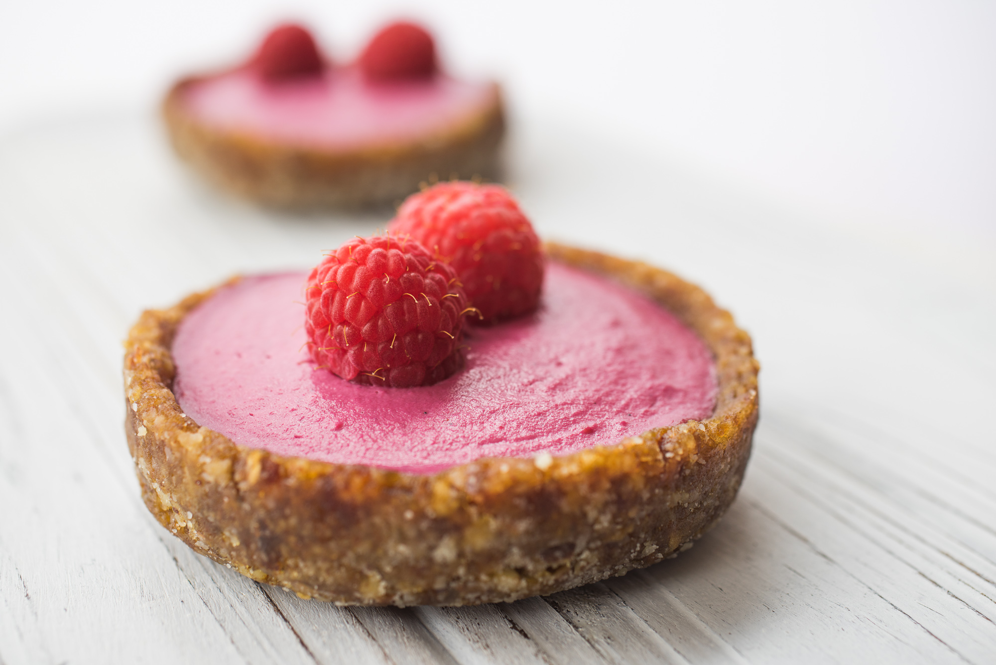 2 Red fruit tarts topped with raspberries