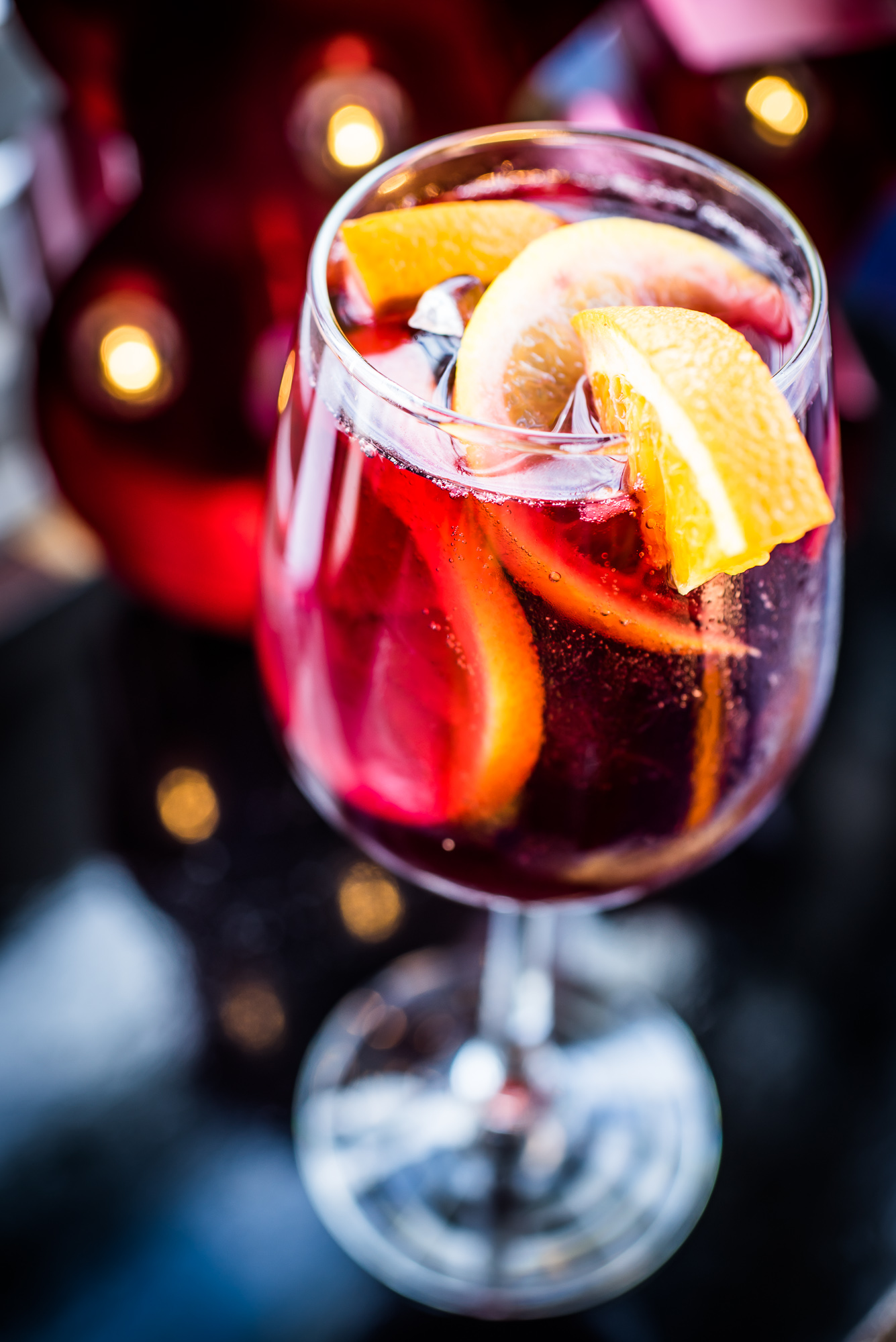 A glass of a red drink topped with orange slices