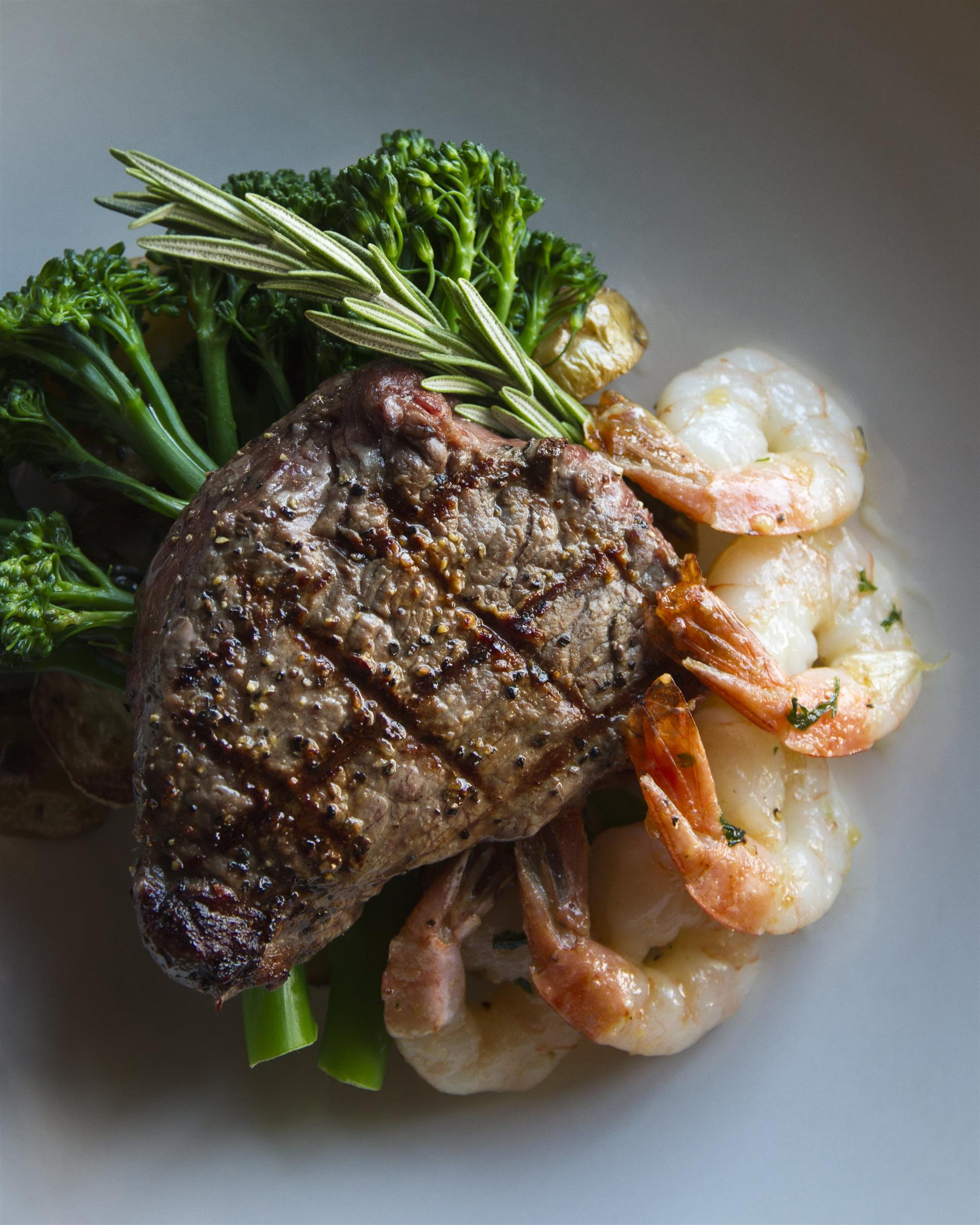 cooked steak on a plate with five shrimp and broccoli