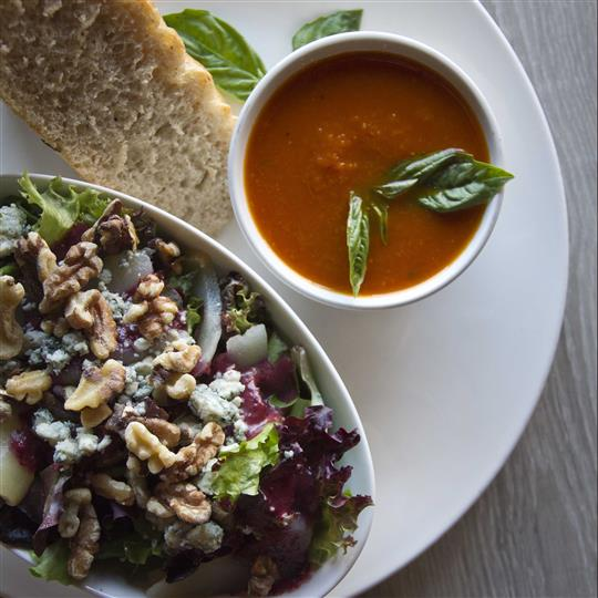 Salad and soup served with a slice of bread