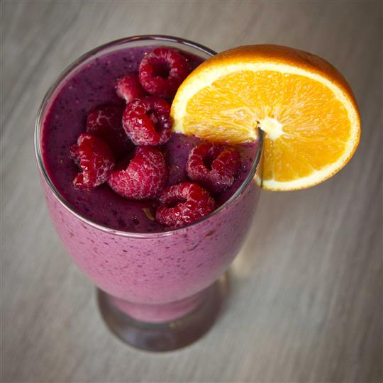 A red fruit smoothie topped with raspberries and a slice of orange