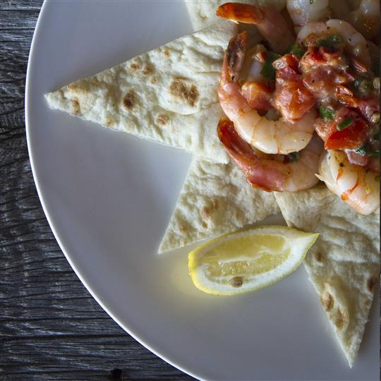A tortilla cut in a star shape topped with shrimp served with a lemon wedge