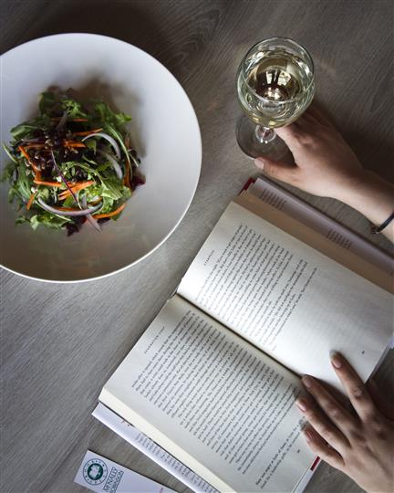 Someone reading a book having a salad and a glass of white wine