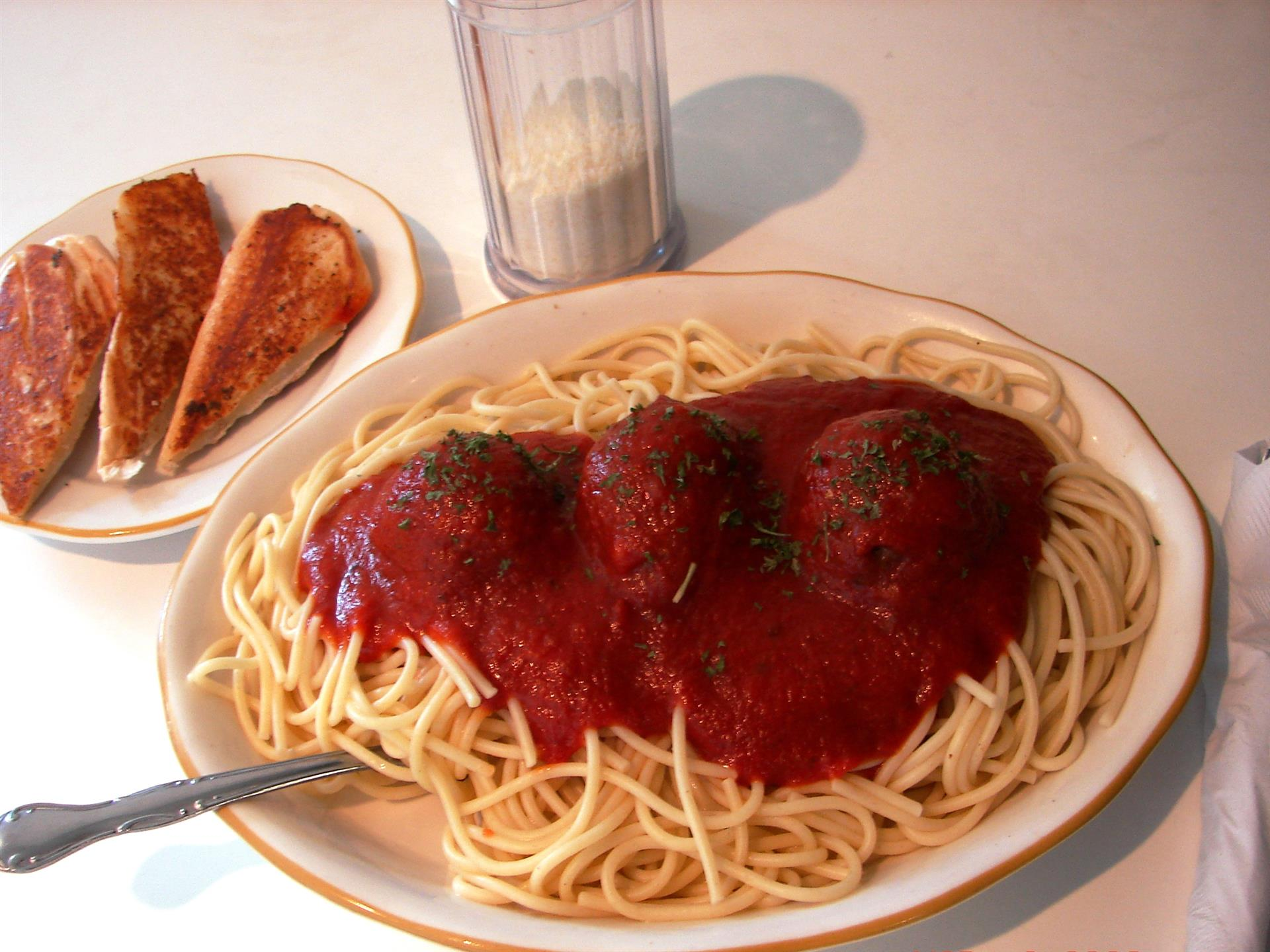 Spaghetti with meatballs on white dish with side of bread.