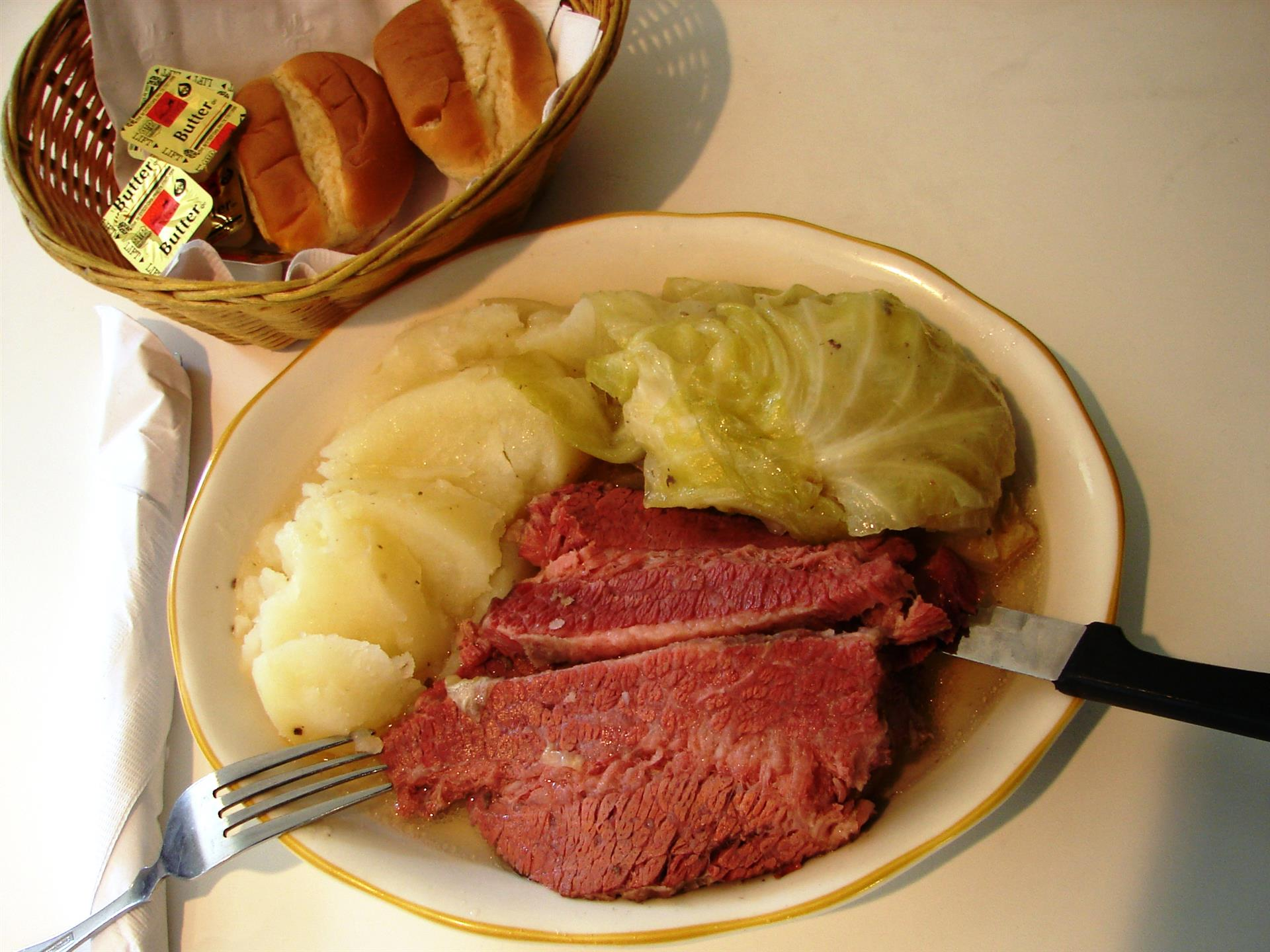 Corned beef and cabbage with mashed potatoes, side of dinner rolls in basket.