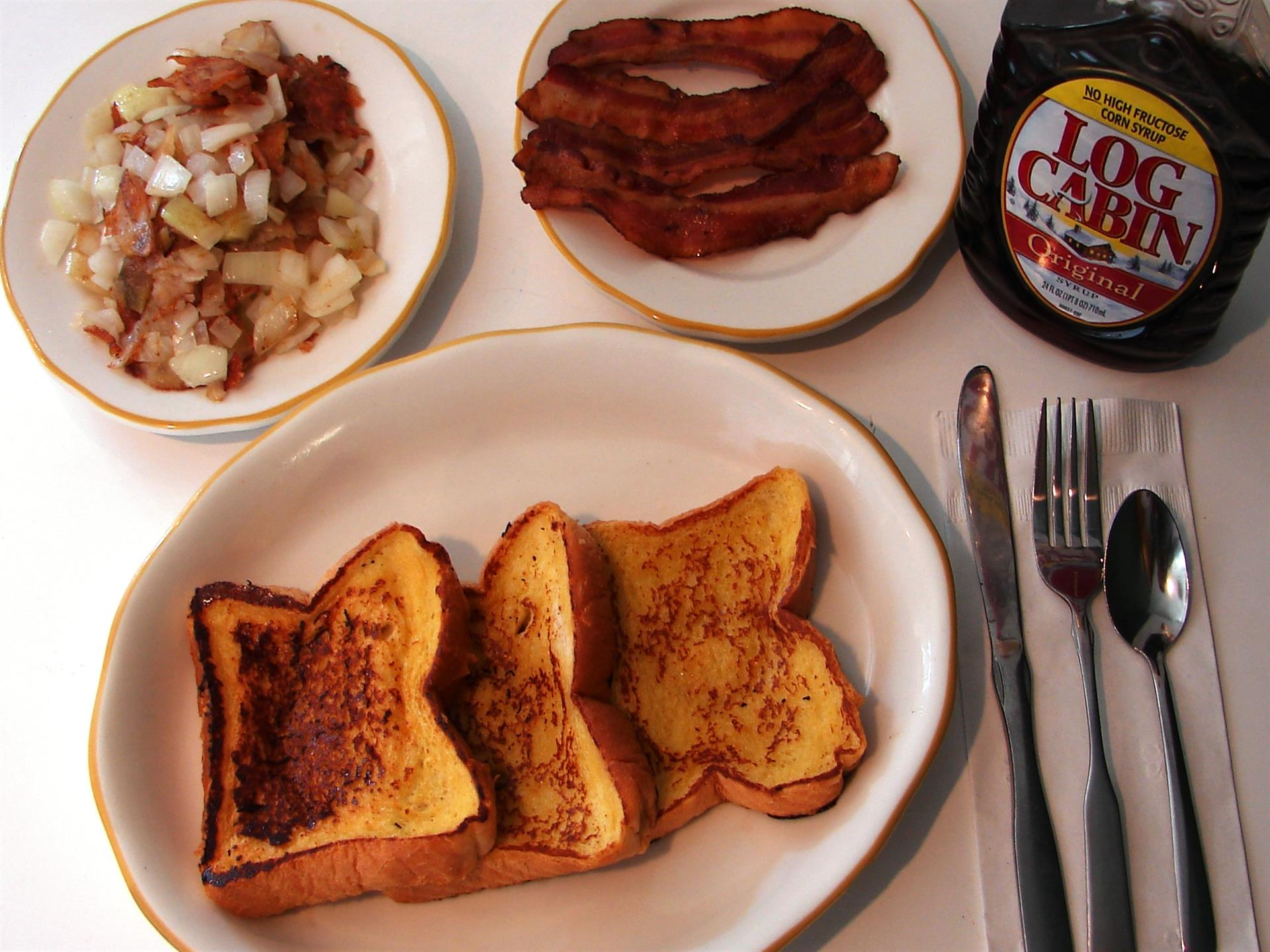 White table with plates of french toast, hash browns, bacon. Syrup and utensils on napkin.