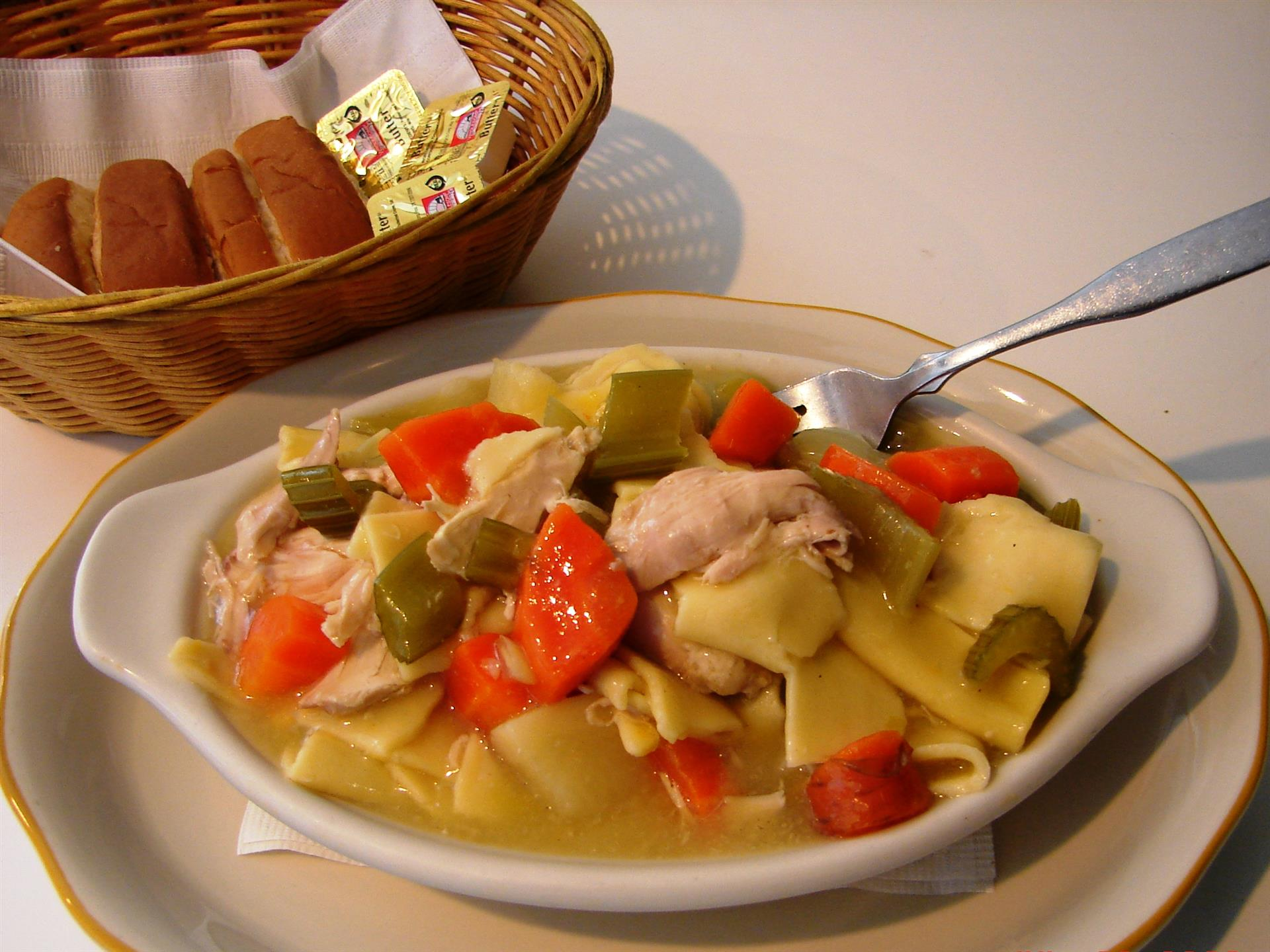 Chicken noodle soup with side of rolls in basket
