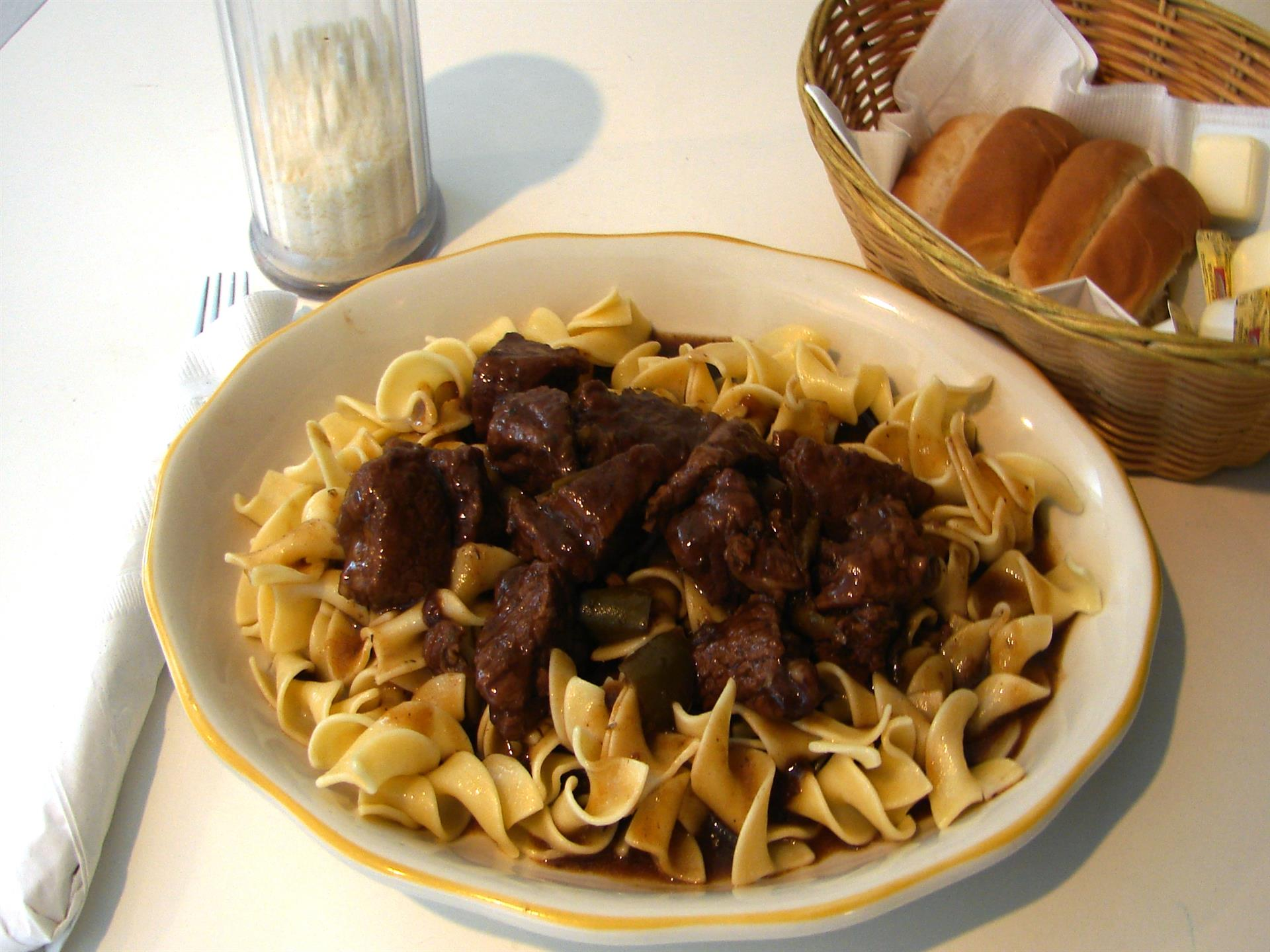 Noodles with beef in white dish, dinner rolls in basket.