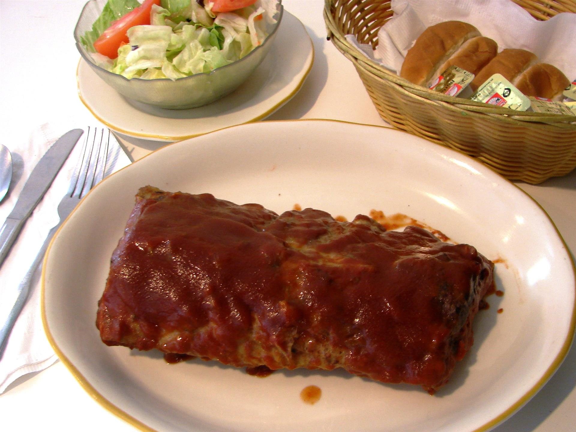 Plate of ribs with barbecue sauce. Side salad, rolls in basket.