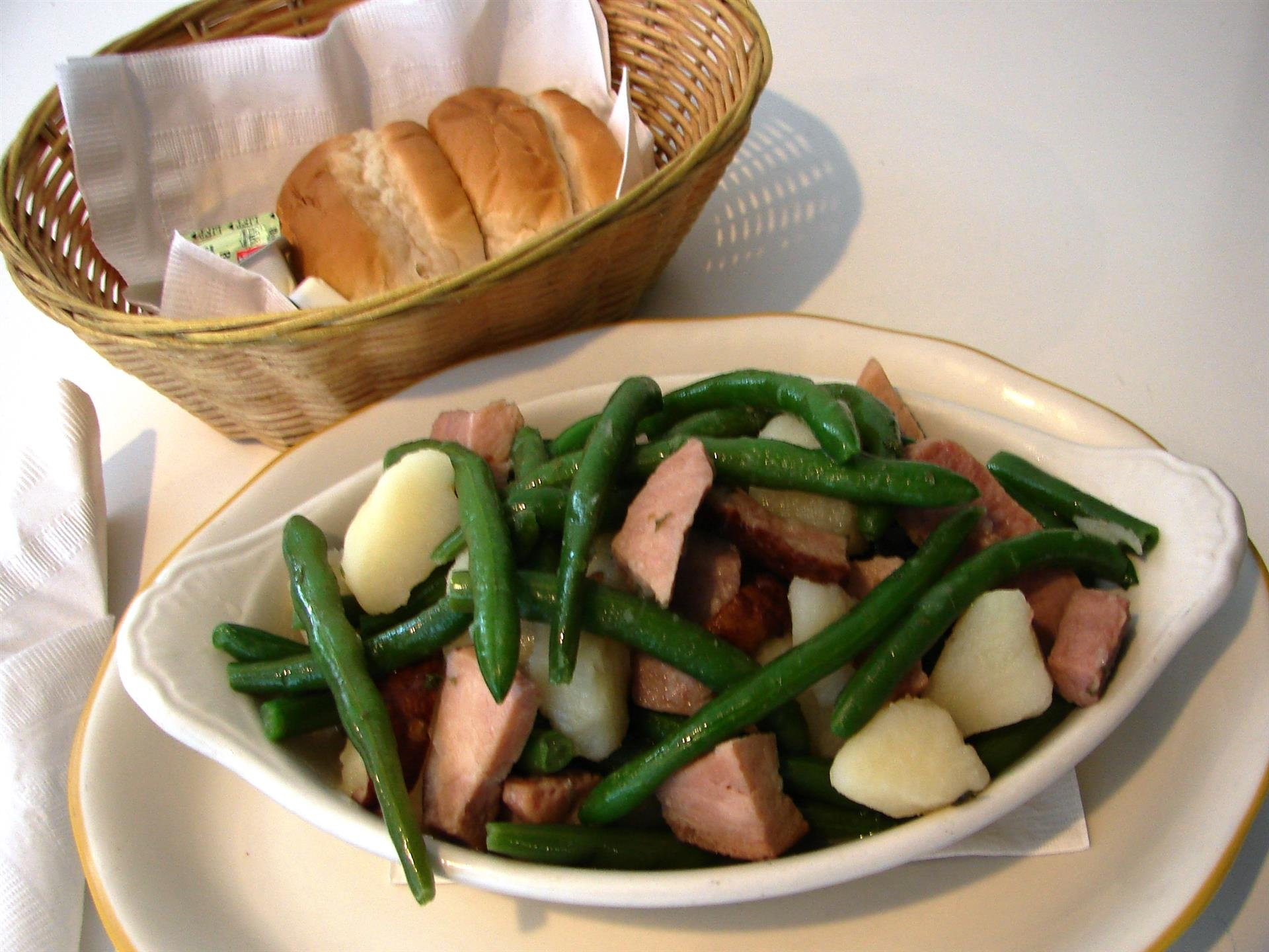 Green bean, pork, potato on white dish with basket of rolls and butter.
