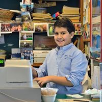 Boy standing behind desk in office