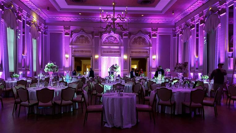 inside banquet hall with set tables and purple lights