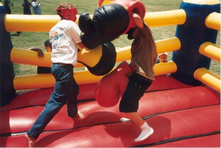 two kids fighting in a blow up boxing ring