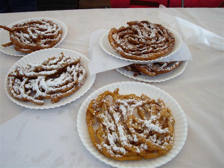 fried dough on a plate with powdered sugar