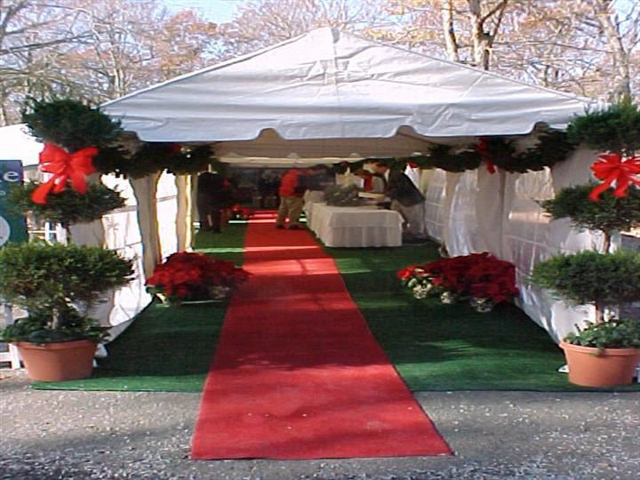 rec carpet event with red flowers under a white tent