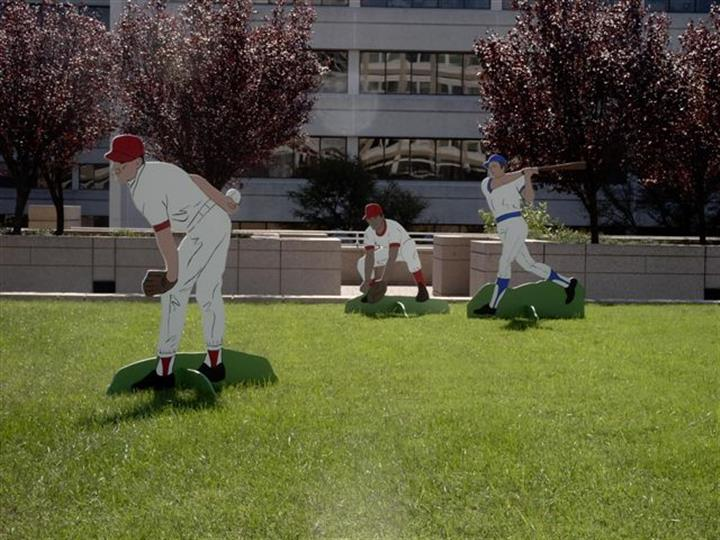 baseball lifesized figurines playing on the green