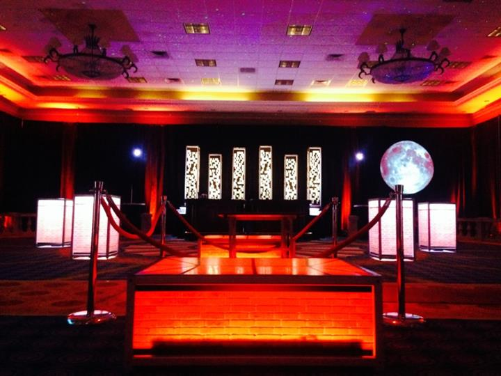 event venue with lite up red carpet and velvet ropes blocking the enterance