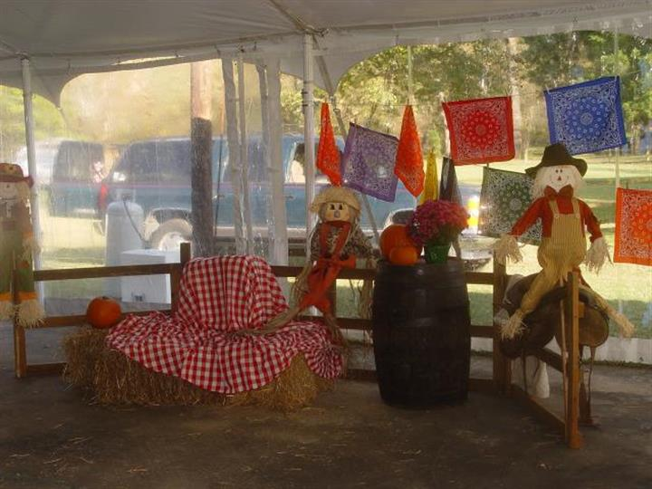 inside of a tent with hay and scarecrows