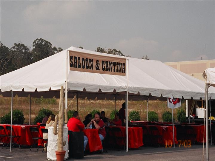 saloon and cantina tent with cactuses and red tables