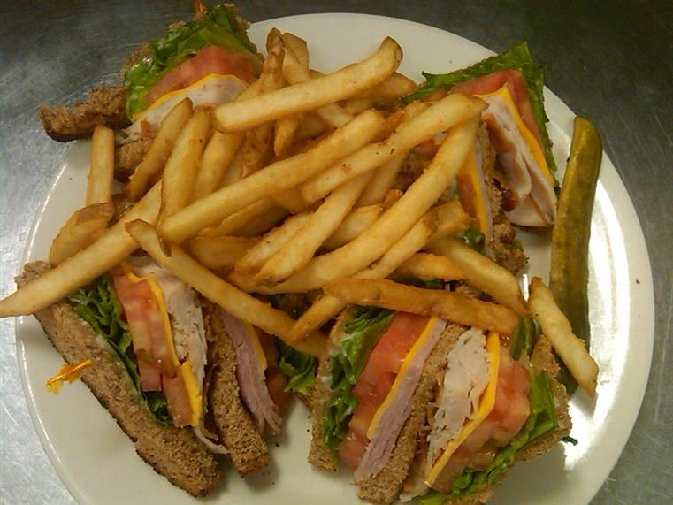 turkey club sandwich cut in half with cheese, lettuce and tomato with a side of french fries