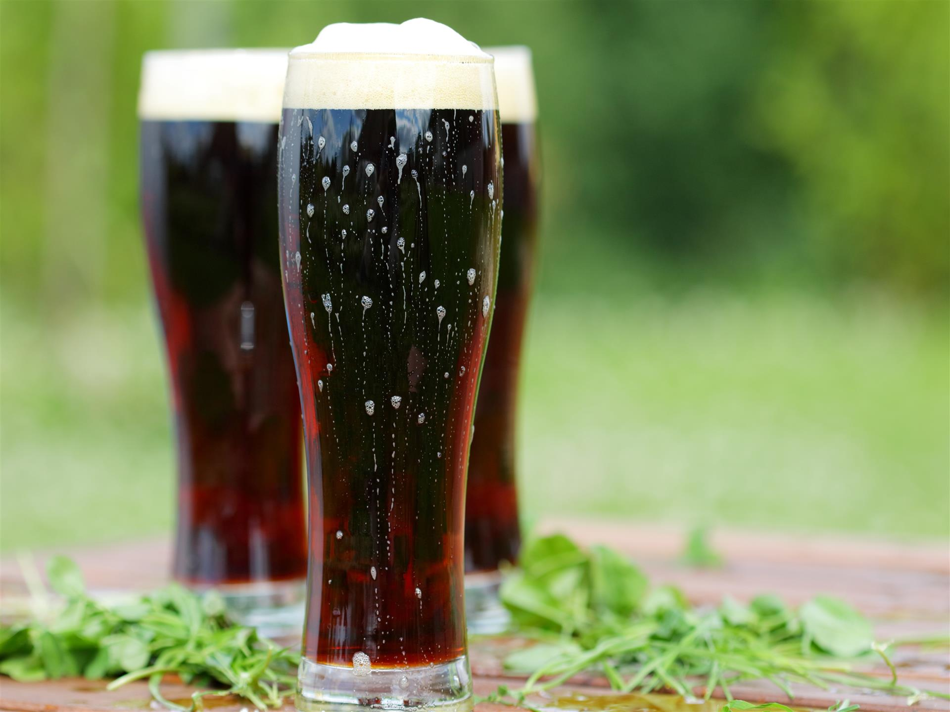 three tall glasses of dark beer