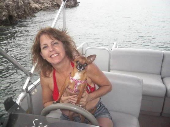 female in a boat holding a dog