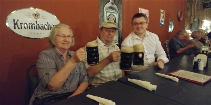people holding mugs of beer