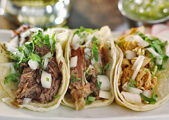 3 soft-shell Shredded beef tacos topped with diced onion and cilantro