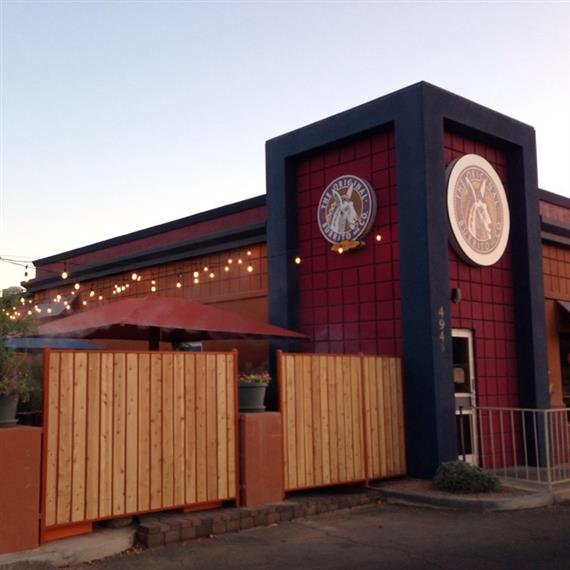 The outside of the building with a fenced off patio and string lights for decoration