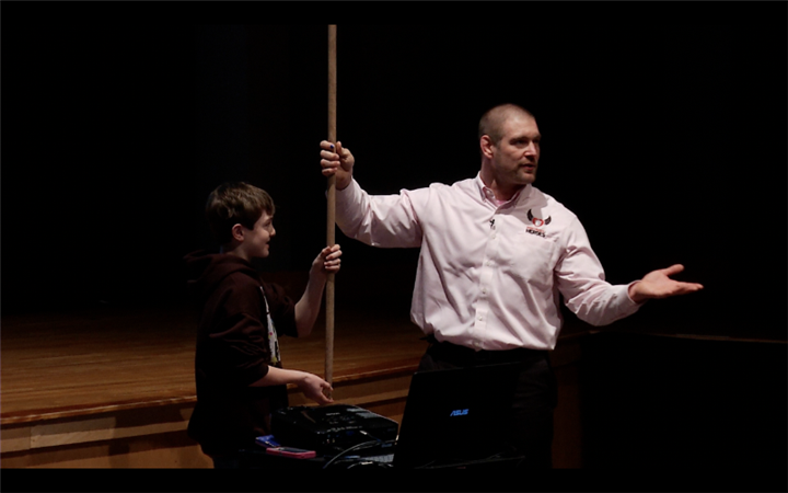 Tom murphy with elementary student holding a stick together