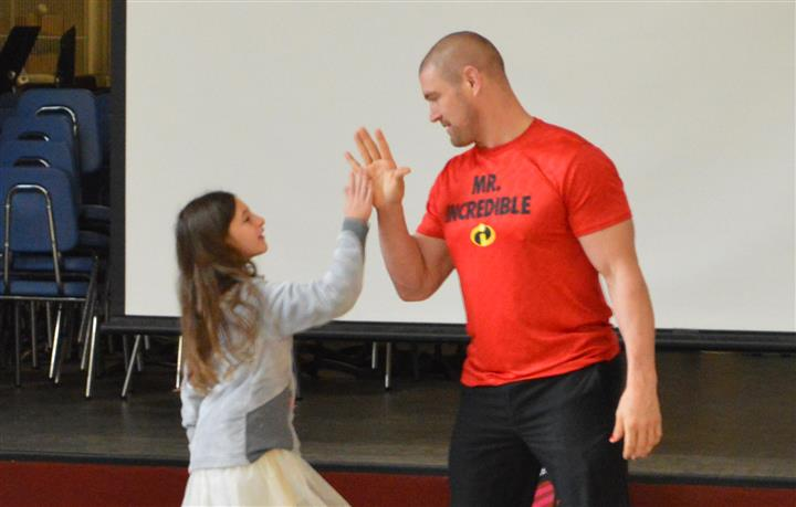 Tom murphy giving high five to elementary student