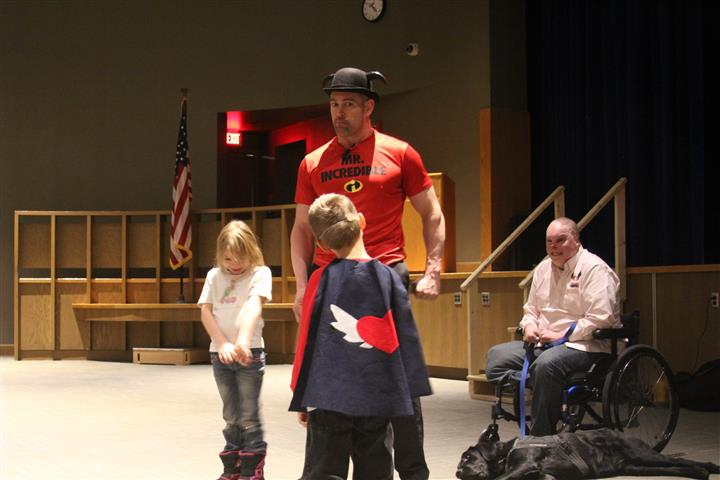 Tom murphy with elementary students roleplaying on stage