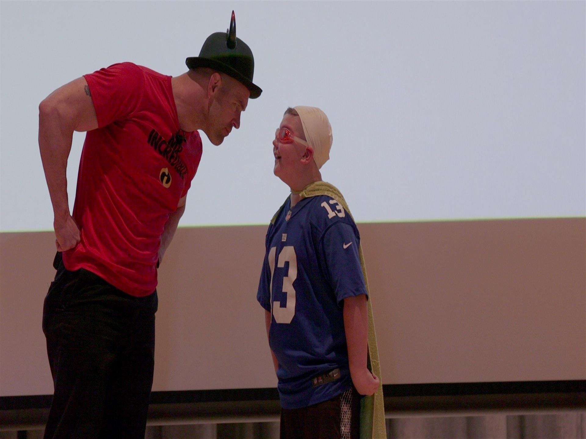Man in hat facing young boy wearing cape