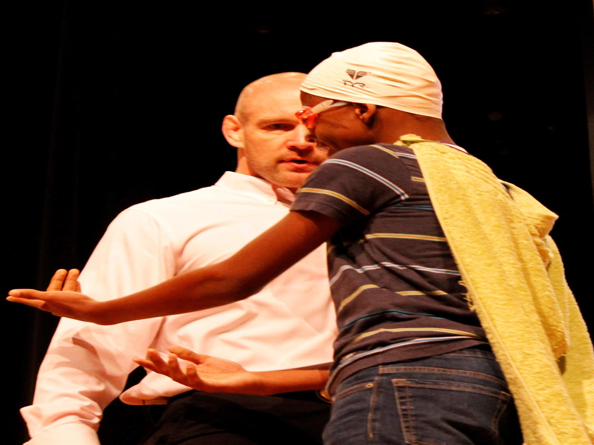 Man with young boy on stage in cape