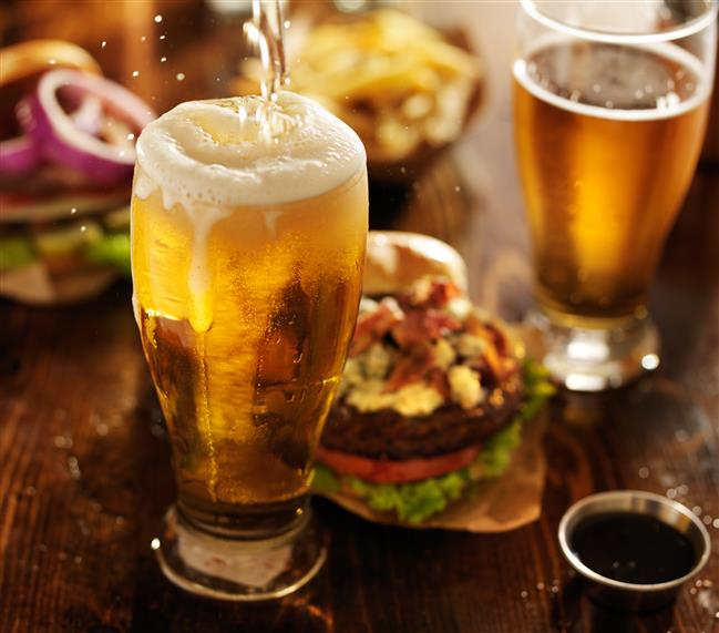 beer being poured into a glass, with a cheeseburger and another beer in a glass on a table